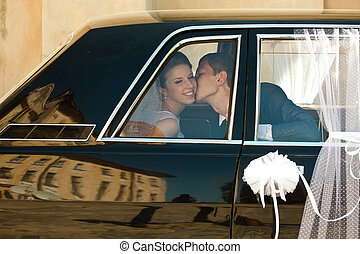 Bride smiles while groom kisses her sitting in the limousine