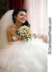 Smiling bride with the bouquet.