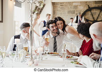 Bride Socialising With Guests At Her Wedding Meal