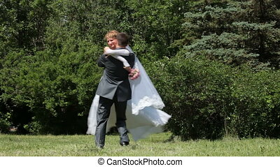bride spinning groom holding her in his arms in the park