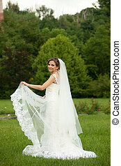 Bride spreads her veil standing on the green lawn