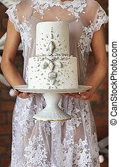 Bride standing near the brick wall holding wedding cake