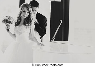 Bride stands thoughtful behind a piano while groom hugs her from behind
