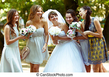 Bride talks with bridesmaids posing in the park