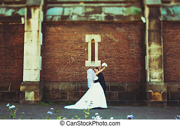 Bride ties her hands along groom's neck kissing him behind an old wall