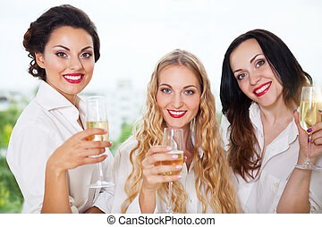 Bride to be and bridemaids holding glass with champagne...