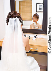 Bride to be applying make up in bedroom - Bride to be is...