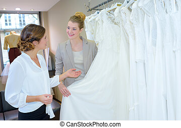 bride-to-be shopping for wedding dresses at bridal shop