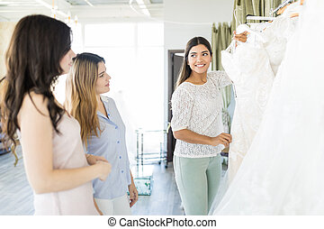 Bride To Be Showing Wedding Gown To Friends - Smiling woman...