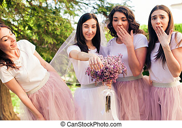 Bride-to-be shows the ring at hen party. Girls in tulle...