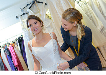 bride-to-be trying on wedding dress at a dress fitting