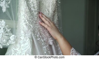 Bride touching her dress with hand