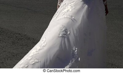 Bride walking in a city and waving dress