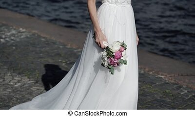 Bride walking on embankment