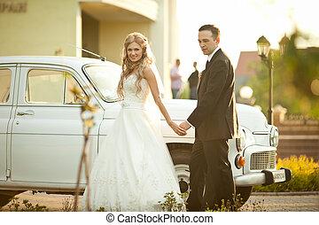Bride walks behind an old car holding groom's hand