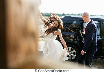 Bride walks dancing in the sunlight while groom closes a car behind her
