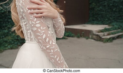 Bride wear full length white wedding dress outdoor and pose for photoshoot. Blonde model woman look at camera. New fashion collection. Concept magazine, gown, romantic.