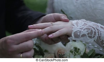 Bride wear ring on groom's finger. The groom puts the wedding ring to finger of the bride. marriage hands with rings. birde wears the ring on the finger of the groom