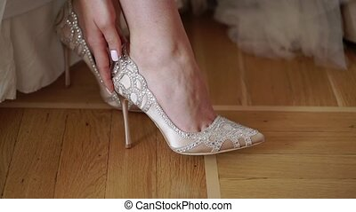 Bride wearing bridal wedding shoes sitting on bed