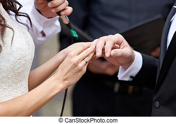 bride wears a wedding ring on finger of groom