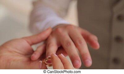 Bride wears on the groom's finger a wedding wear close up