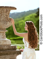 Wedding outdoor portrait of gorgeous brunette bride with long wavy hair wearing