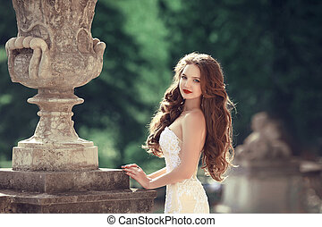 Wedding outdoor portrait of gorgeous brunette woman with long wavy hair