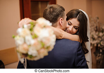 bride with a bouquet hugs bridegroom, while he kisses her