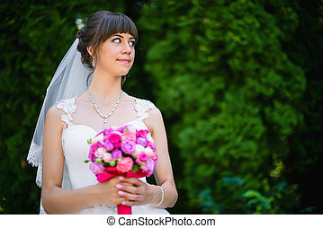 bride with a bouquet of roses in the park