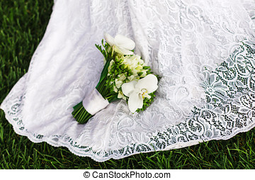 Bride with a bouquet of white Orchid on the wedding dress