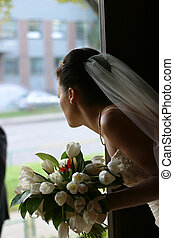 Bride with a bouquet - The bride with a bouquet looks out a...