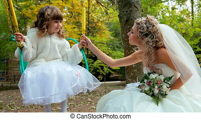 bride with a little girl on a swing