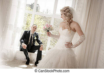 bride with a wedding bouquet from roses and the groom sitting at a window on a background