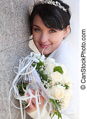bride with bouquet at wall