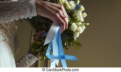 Bride holding bouquet with ribbons