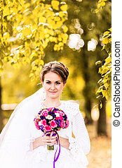 Bride with bouquet posing in sunny autumn park