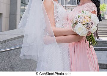 bride with bridesmaid in pink dress hugging