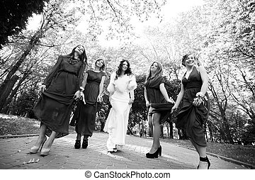 Bride with bridesmaids dancing in the park