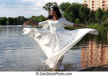 Bride with flying dress at pond