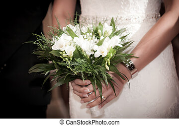 Bride with groom holding a wedding bouquet