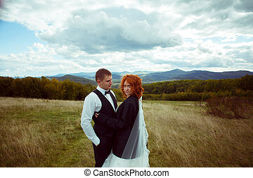 Bride with red curly hair hugs a groom standing on the field with great mountain landscape behind them