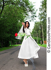 Bride with red flying flower at road