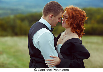 Bride with red hair looks seductive being hugged by a groom