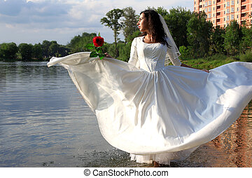 Bride with red rose in flying dress at pond