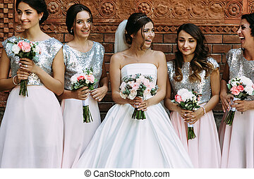 Bride with the bridesmaids in the shining dresses