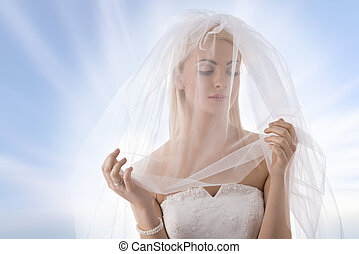 bride with veil on the face looks at left