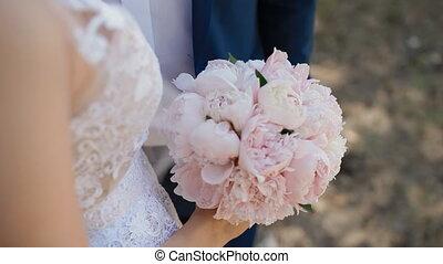 Bride with wedding bouquet of pink peones