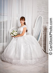 Bride with wedding bouquet sits in an armchair near window