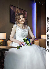 Bride with wedding bouquet sitting on the chair in hotel