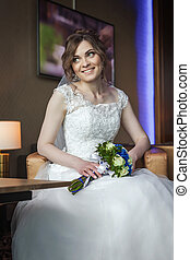 Bride with wedding flowers sitting on the armchair and smiling